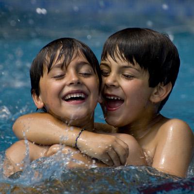 dos nens juguen a la piscina